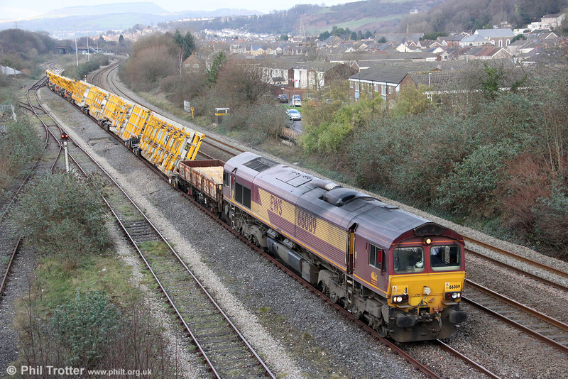 66089 departs from Briton Ferry Yard with 6X44, 0728 Westbury to Margam on 14th January 2012. The train consists mainly of Network Rail's new tilting track wagons which permit pre-assembled and tested pointwork which would otherwise be out of gauge, to be delivered to the worksite, in this case at Margam Moors.