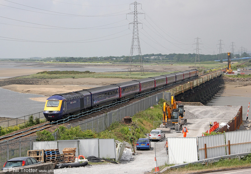Carillion plc. is carrying out preparatory work for the rebuilding of Loughor Viaduct which will form part of the £40m project to redouble the line from Cockett West to Llandeilo Junction. Final planning permission is now in place for the viaduct to be renewed, which is understood to have been the last major hurdle for the work to go ahead. Early activity has included the construction of a quay (right) for barges which will transport materials to and from the worksite. This was the scene on 2nd June 2012 with 43022 heading 1L62, the summer only 1000 Pembroke Dock to London Paddington.