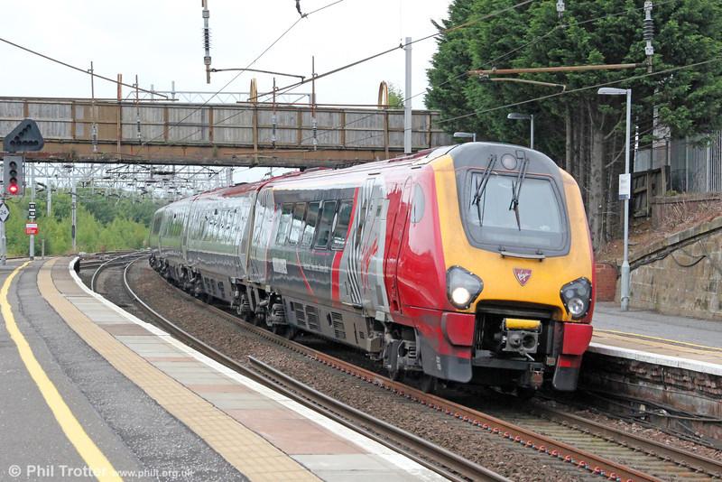 Displaying its Bombardier livery, 221115 'Polmadie Depot' passes Motherwell forming 1M54, 1052 Edinburgh Waverley to Birmingham New Street on 5th August 2012.