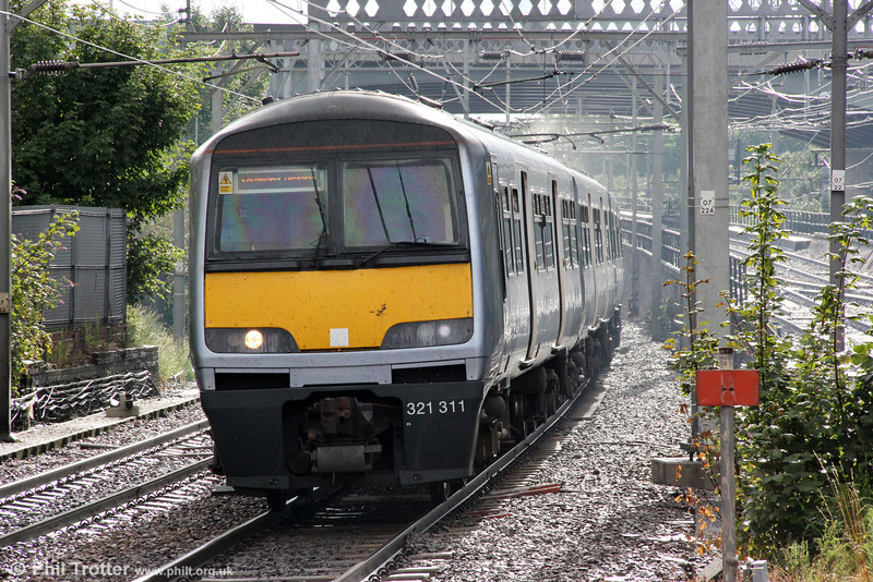 In a moment of sunshine following a heavy downpour, 321311 approaches Ilford forming 1Y28, 1702 London Liverpool Street to Ipswich on 25th August 2012.