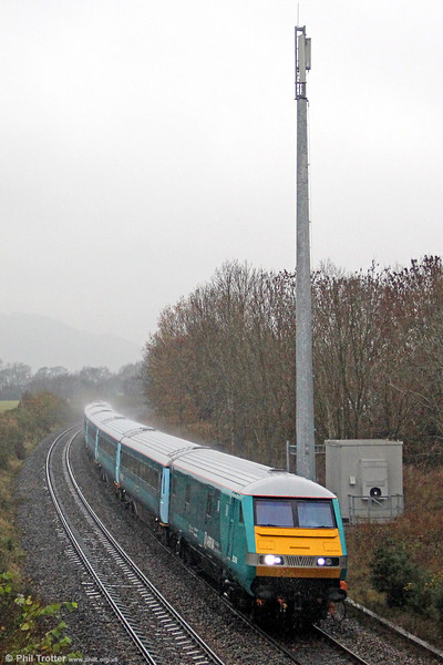 With the rain bouncing off the roof, DVT 82306 leads 'Rugex' 1V41, 0807 Holyhead to Cardiff Central through Penpergwm on 24th November 2012. Power was provided by 67003.