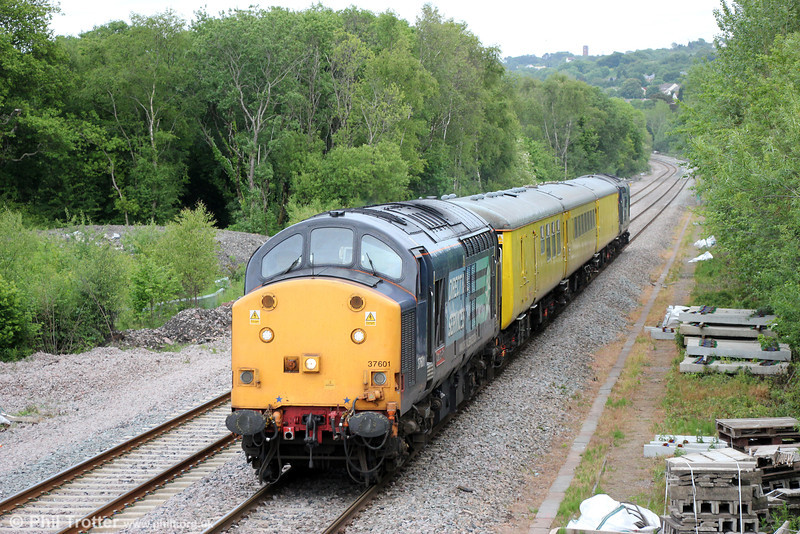 37601 'Class 37 - Fifty' passes Gowerton with 1Q13, 1810 Landore TMD to Newport ADJ via Llandeilo Junction, Cwmbargoed, Cardiff Bay and Coryton on 11th June 2013. The train consisted of Network Rail Brake Force Runner 99666, Radio Survey Coach 977997 and Staff Coach 977969. Classmate 37605 was at the rear.