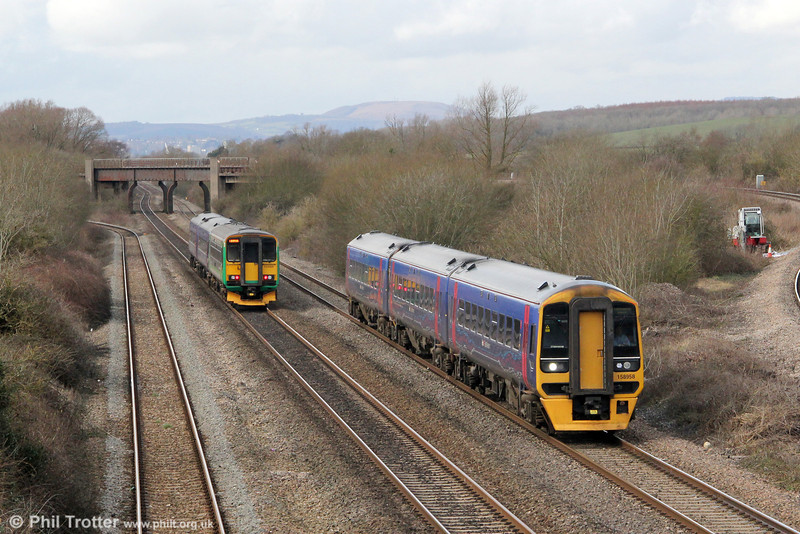 158958 forming 1F13, 1130 Cardiff Central to Portsmouth Harbour, passes 2U12, 1012 Taunton to Cardiff Central (with ex-LM 153325 at the rear) at Llandevenny on 16th March 2013.