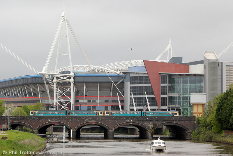 ATW class 142 and 143 units cross the River Taff at Cardiff with the Millennium Stadium as a backdrop and the 'Aquabus' approaching on 10th May 2013.