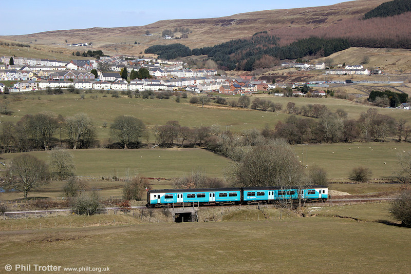 The village of Abertysswg forms a backdrop to 150208 in the landscape at Pontlottyn with 2R14, 1402 Penarth to Rhymney on 6th April 2013. McLaren Colliery once stood on the site of the fenced off rugby ground (centre right). The row of terraced houses above the rugby ground are still referred to as McLaren Cottages.