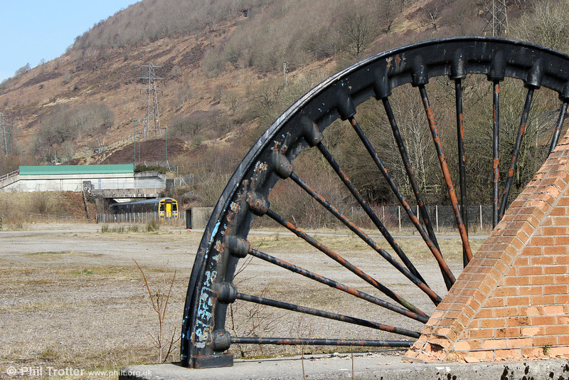 Marine Colliery, Cwm was the last deep mine to work in the Ebbw Valley. After it closed in March 1989 the area was cleared and the winding wheels were sectioned and placed over the shafts. 158833 passes the site with 2F30, 1240 Ebbw Vale Parkway to Cardiff Central on 6th April 2013.