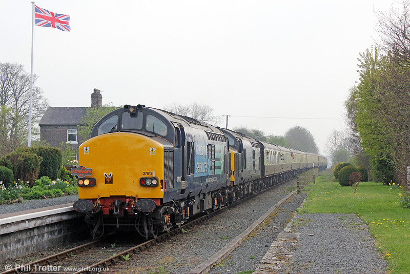 DRS 37612 and 37611 pass the well kept station at Dolau with Pathfinder Tours 1Z50, 1646 Llandrindod Wells to Eastleigh, 'The Heart of Wales Meanderer' on 21st April 2014.