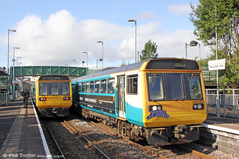 Sisters: 142082 passes Mountain Ash with 1Z42, 1200 Pontypridd to Pontypridd via Treherbert and Aberdare, the Branch Line Society's 'Cardiff Valley Pacer Farewell/Farwelio â Phacer Cymoedd Caerdydd' railtour of 6th October 2019. 142083 waits at the rear of 2A12, 1256 Barry Island to Aberdare.