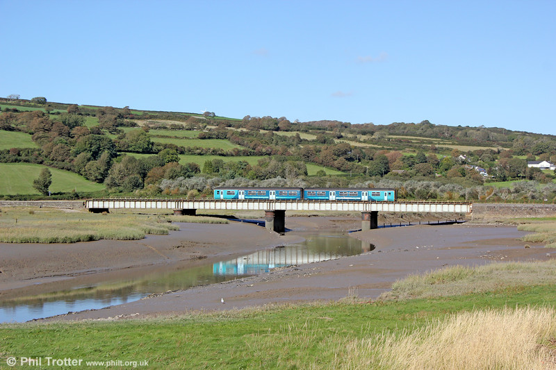 2E17, 1309 Pembroke Dock to Swansea crosses the Gwendraeth Fach at Kidwelly on 17th September 2019.
