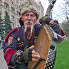 An elderly Ukrainian street musician dressed in traditional Cossack costume performs on a domra, a long-necked string instrument, to earn extra money, in downtown Kiev, Ukraine. (AP Photo/Efrem Lukatsky)