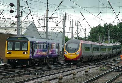142018 arrives at Carlisle as Pendolino 390023 departs
