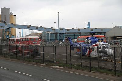 G-BWWI (Aerospatiale Super Puma) minus rotor blades + 2 old London buses parked up at Seaforth docks - 14/04/12.