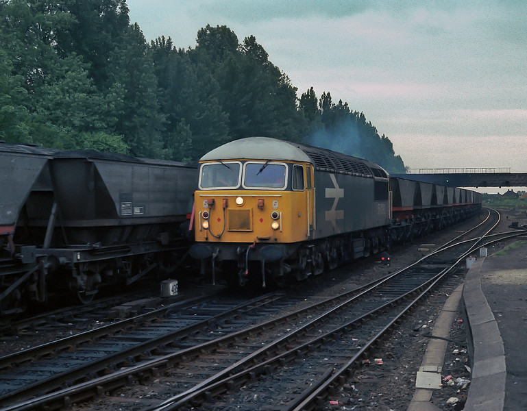 Empty coal hoppers behind 56092 pass a southbound loaded service at York on 11 June 1985