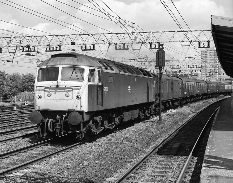 47008 brings the newspaper vans back up to town to be loaded with that night's papers seen passing Stratford on 16 May 1986