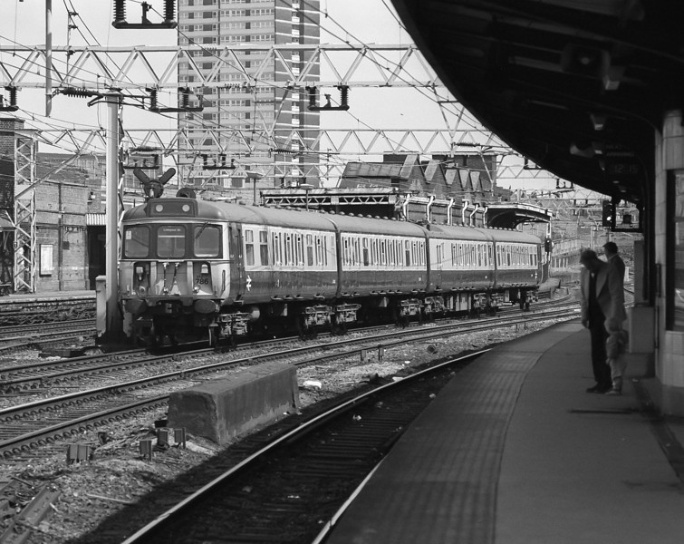 The next generation of spotter looks on (?) as 312786 runs through Stratford on 16 May 1986