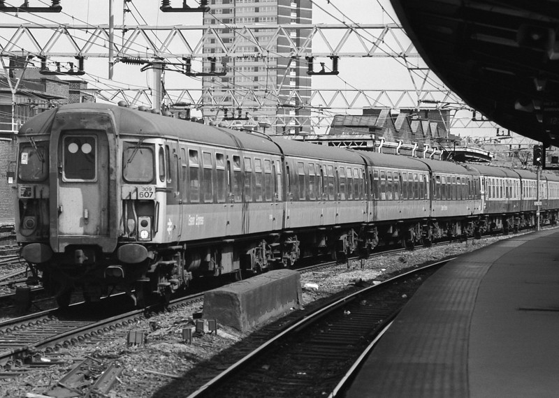 309607, in 'Jaffa Cake' livery, and 309621 head to Liverpool Street at Stratford on 16 May 1986