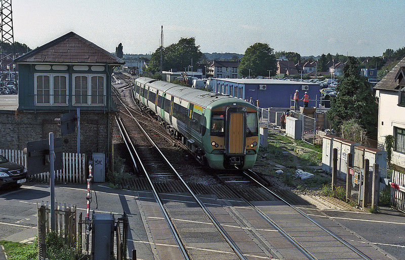 Southern Electrostar 377 passes the old signal box at Havant on 20 September 2006 while signs of the building work for the new power signalling centre are evident to the right