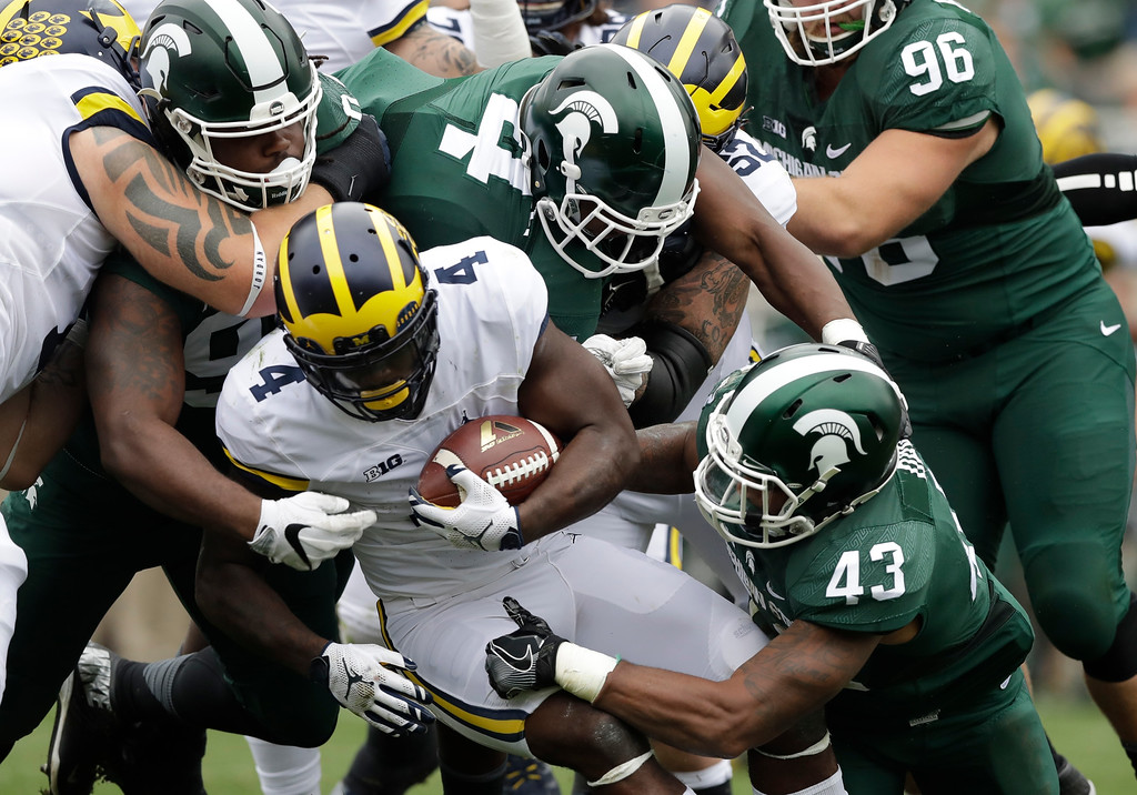. Michigan running back De\'Veon Smith (4) is topped by Michigan State defensive lineman Malik McDowell (4) and linebacker Ed Davis (43) during the first half of an NCAA college football game, Saturday, Oct. 29, 2016, in East Lansing, Mich. (AP Photo/Carlos Osorio)