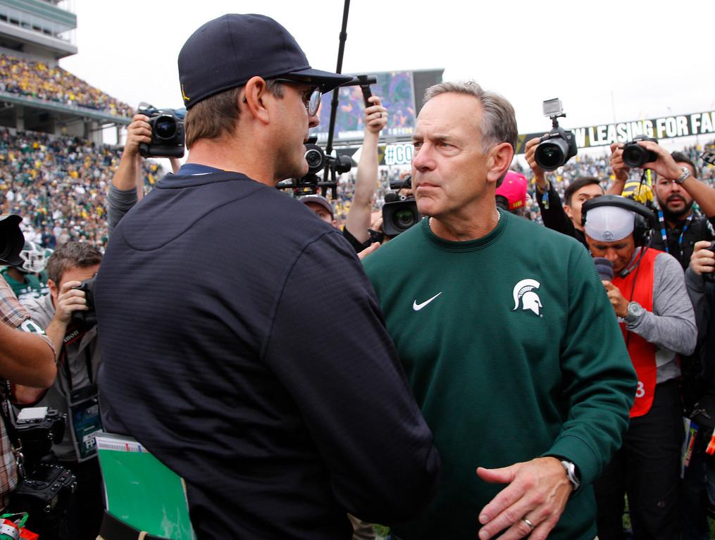 . Michigan coach Jim Harbaugh, left, and Michigan State coach Mark Dantonio shake hands following an NCAA college football game, Saturday, Oct. 29, 2016, in East Lansing, Mich. Michigan won 32-23. (AP Photo/Al Goldis)