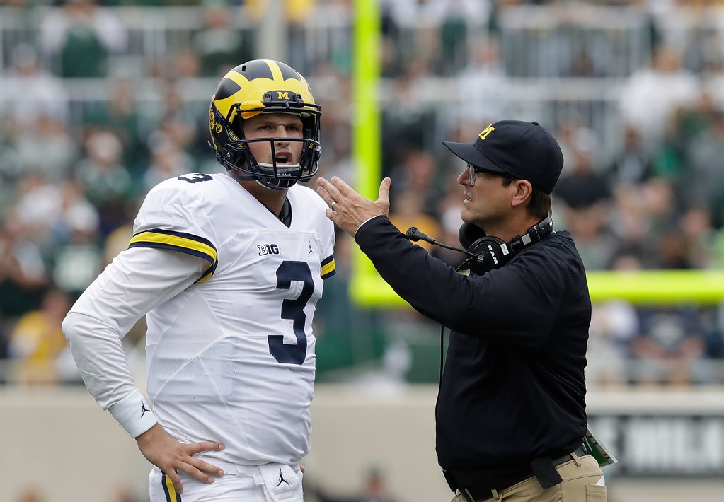 . Michigan head coach Jim Harbaugh talks with quarterback Wilton Speight (3) during the first half of an NCAA college football game against Michigan State, Saturday, Oct. 29, 2016, in East Lansing, Mich. (AP Photo/Carlos Osorio)