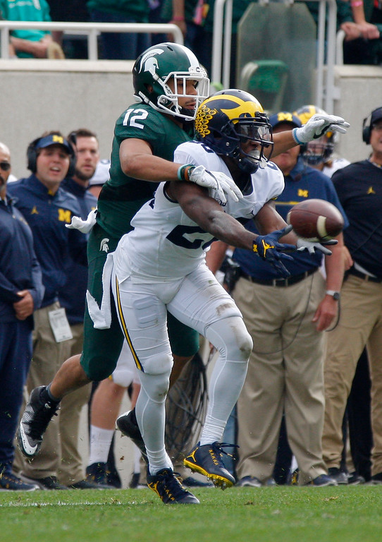 . Michigan\'s Jourdan Lewis, right, intercepts a pass intended for Michigan State\'s R.J. Shelton (12) during the second quarter of an NCAA college football game, Saturday, Oct. 29, 2016, in East Lansing, Mich. Michigan won 32-23. (AP Photo/Al Goldis)