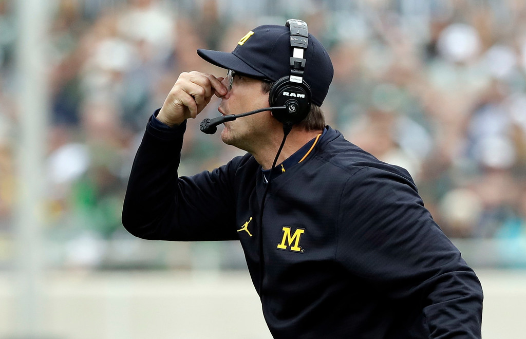 . Michigan head coach Jim Harbaugh gestures from the sidelines during the first half of an NCAA college football game against Michigan State, Saturday, Oct. 29, 2016, in East Lansing, Mich. (AP Photo/Carlos Osorio)
