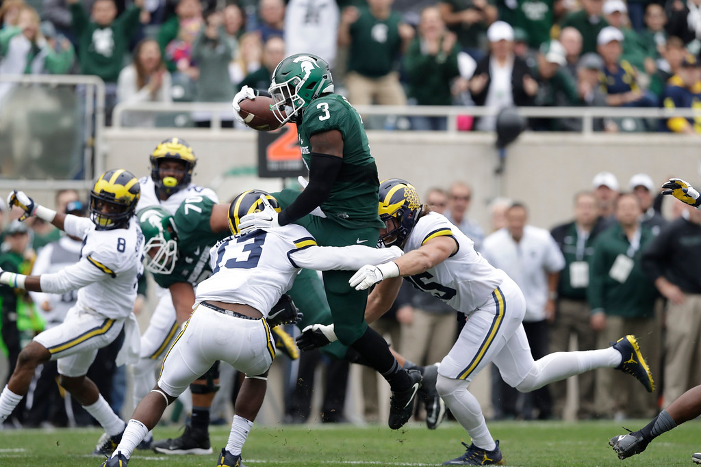 . Michigan State running back LJ Scott (3) is stopped by Michigan safety Josh Metellus (13) during the first half of a college football game, Saturday, Oct. 29, 2016, in East Lansing, Mich. (AP Photo/Carlos Osorio)