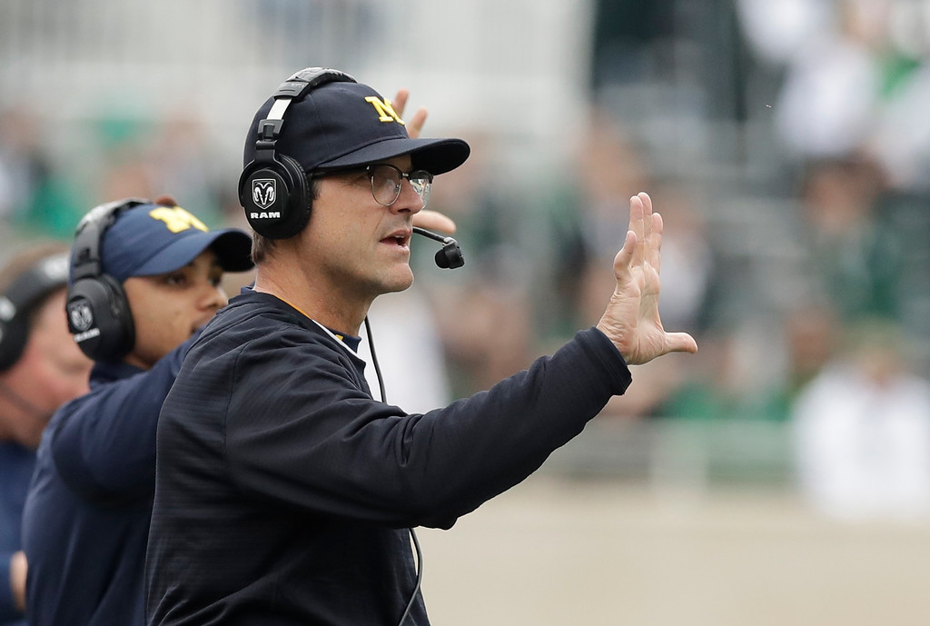 . Michigan head coach Jim Harbaugh signals from the sidelines during the first half of a college football game against Michigan State, Saturday, Oct. 29, 2016, in East Lansing, Mich. (AP Photo/Carlos Osorio)