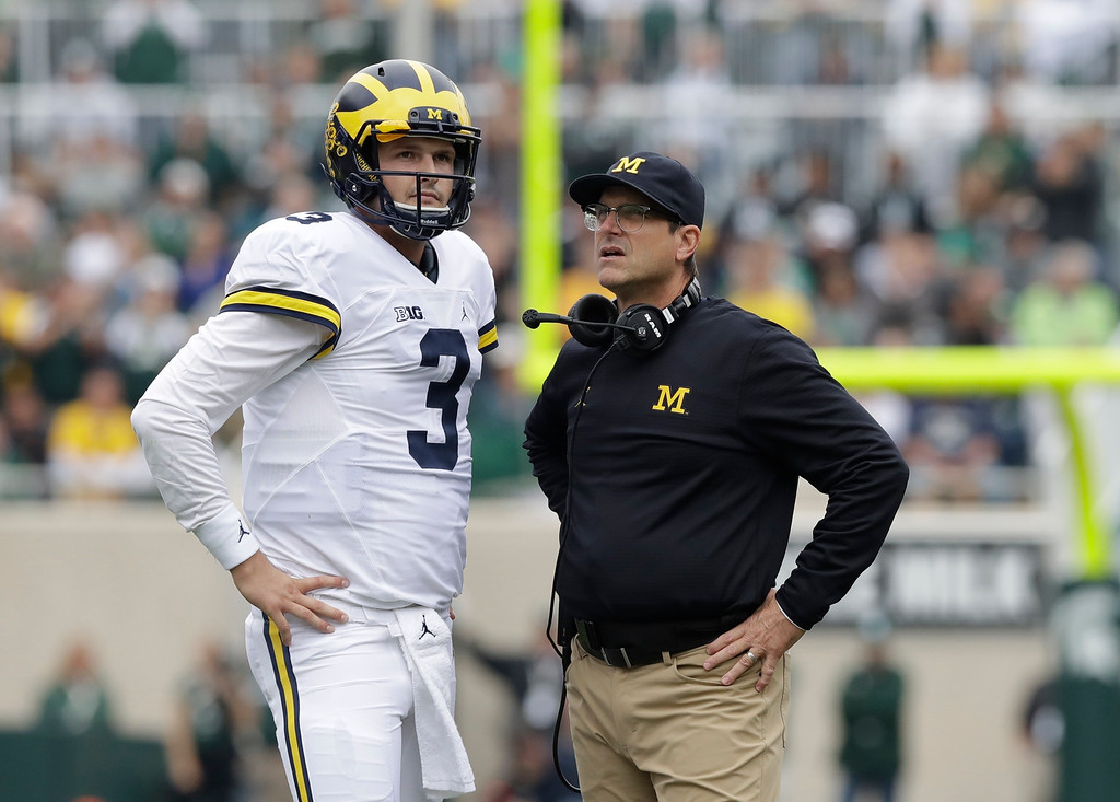. Michigan head coach Jim Harbaugh talks with quarterback Wilton Speight (3) during the first half of a college football game against Michigan State, Saturday, Oct. 29, 2016, in East Lansing, Mich. (AP Photo/Carlos Osorio)