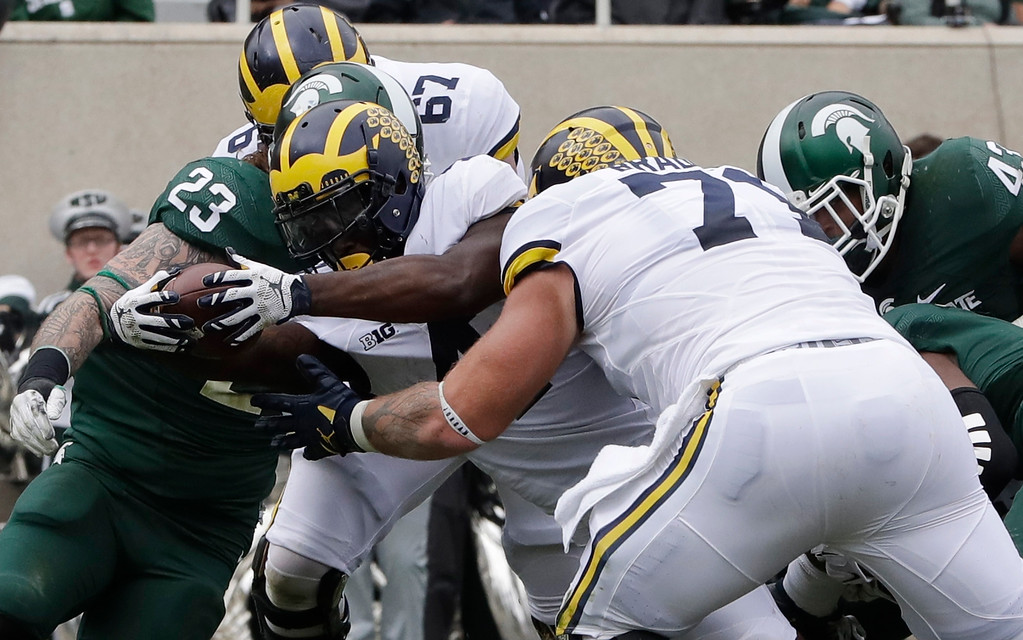 . Michigan running back De\'Veon Smith stretches for a 5-yard touchdown during the first half of an NCAA college football game against Michigan State, Saturday, Oct. 29, 2016, in East Lansing, Mich. (AP Photo/Carlos Osorio)