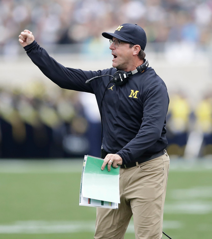 . Michigan head coach Jim Harbaugh gestures from the sidelines during the first half of a college football game against Michigan State, Saturday, Oct. 29, 2016, in East Lansing, Mich. (AP Photo/Carlos Osorio)