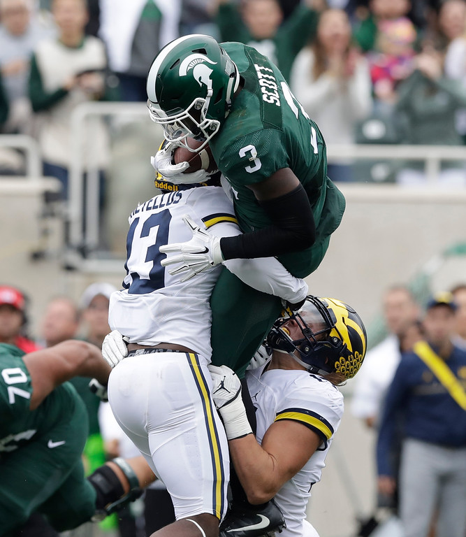 . Michigan State running back LJ Scott (3) is stopped by Michigan safety Josh Metellus (13) during the first half of an NCAA college football game, Saturday, Oct. 29, 2016, in East Lansing, Mich. (AP Photo/Carlos Osorio)