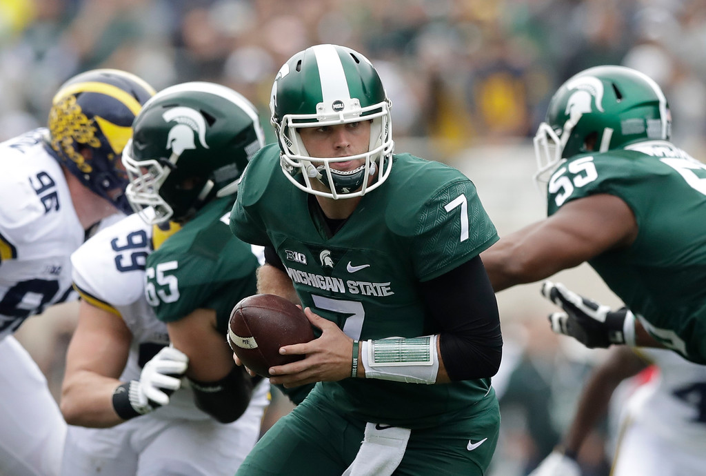 . Michigan State quarterback Tyler O\'Connor (7) gets ready to hands off the ball during the first half of an NCAA college football game against Michigan, Saturday, Oct. 29, 2016, in East Lansing, Mich. (AP Photo/Carlos Osorio)