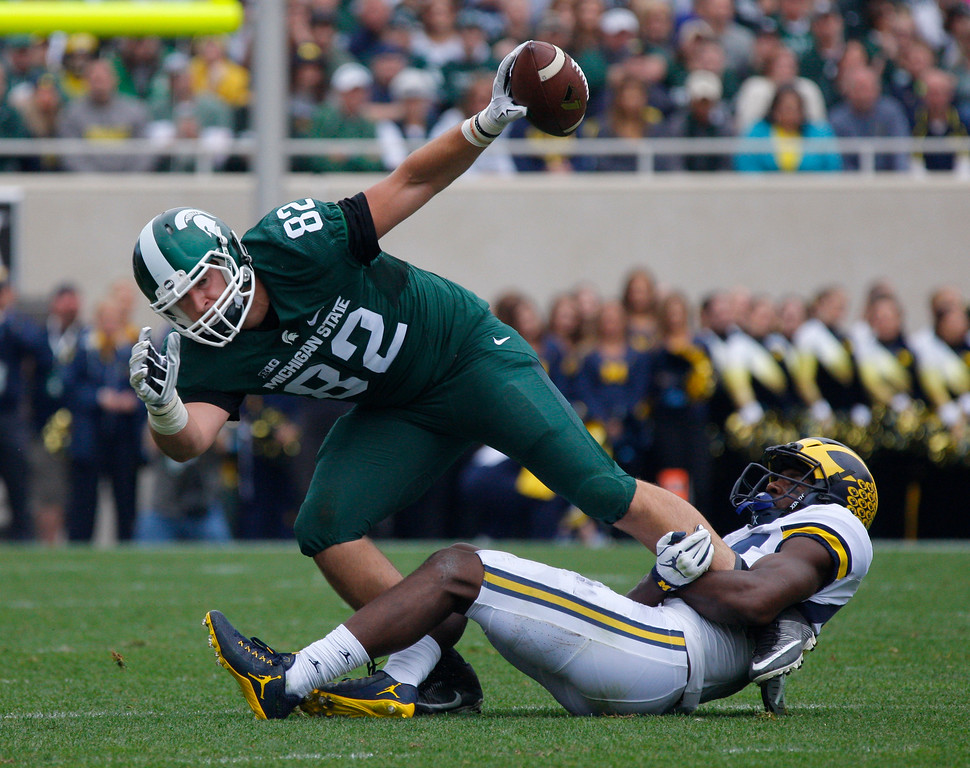 . Michigan State tight end Josiah Price (82) is stopped by Michigan safety Delano Hill during the first quarter of an NCAA college football game, Saturday, Oct. 29, 2016, in East Lansing, Mich. (AP Photo/Al Goldis)