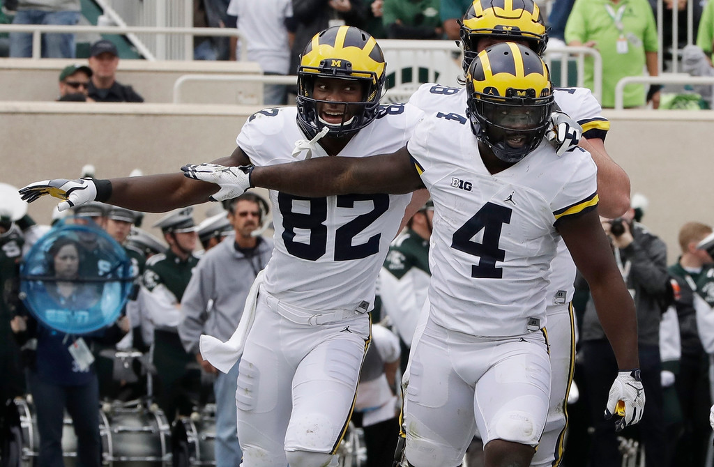. Michigan running back De\'Veon Smith (4) is congratulated by wide receiver Amara Darboh (82) after his 5-yard run for a touchdown during the first half of an NCAA college football game against Michigan State, Saturday, Oct. 29, 2016, in East Lansing, Mich. (AP Photo/Carlos Osorio)
