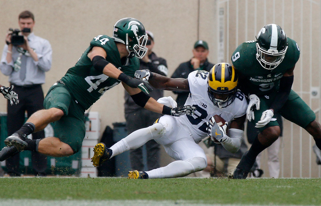 . Michigan\'s Amara Darboh, center, comes down with a reception for a first down between Michigan State\'s Grayson Miller, left, and Montae Nicholson during the second quarter of an NCAA college football game, Saturday, Oct. 29, 2016, in East Lansing, Mich. Michigan won 32-23. (AP Photo/Al Goldis)
