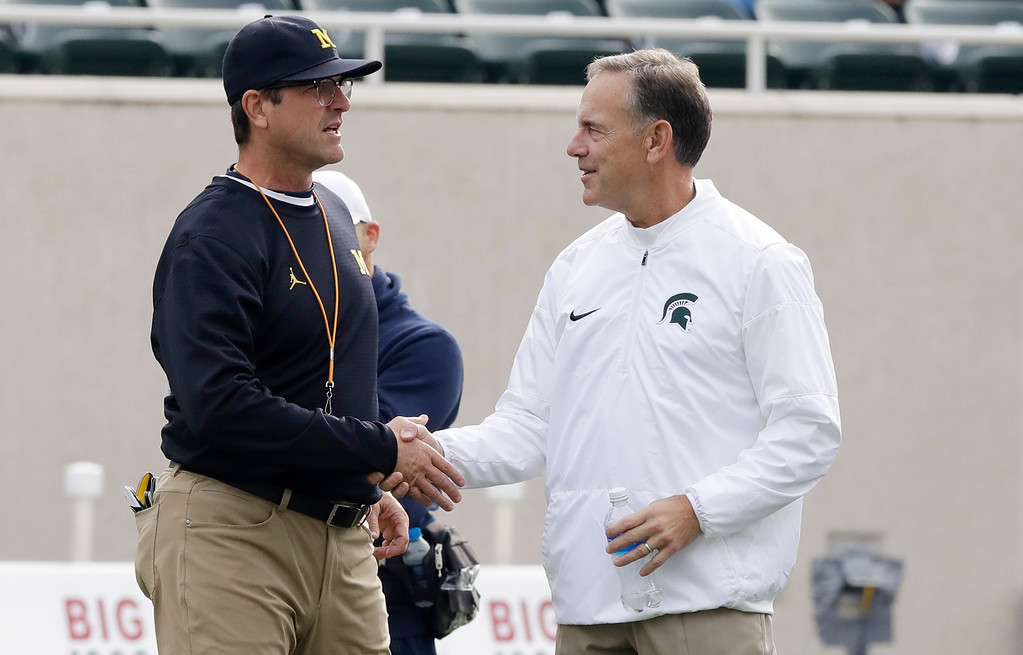 . Michigan head coach Jim Harbaugh, left, greets Michigan State head coach Mark Dantonio at midfield before their college football game, Saturday, Oct. 29, 2016, in East Lansing, Mich. (AP Photo/Carlos Osorio)