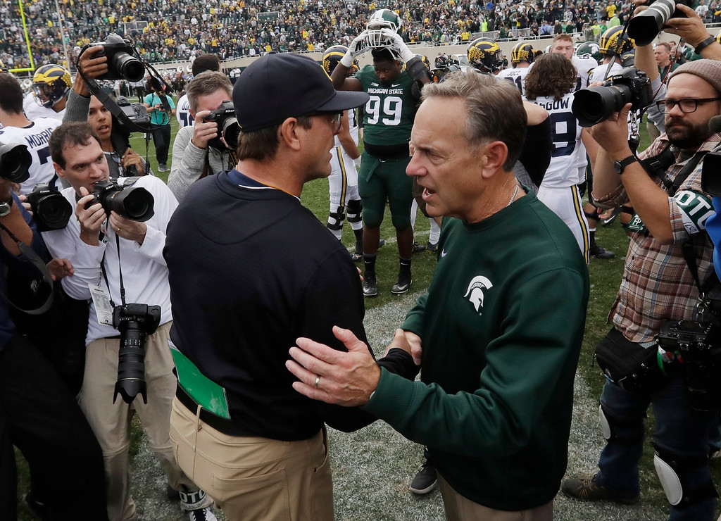 . Michigan head coach Jim Harbaugh, left, meets Michigan State head coach Mark Dantonio after their NCAA college football game, Saturday, Oct. 29, 2016, in East Lansing, Mich. Michigan won 32-23. (AP Photo/Carlos Osorio)