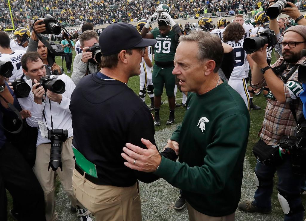 . Michigan head coach Jim Harbaugh, left, meets Michigan State head coach Mark Dantonio after their NCAA college football game, Saturday, Oct. 29, 2016, in East Lansing, Mich. Michigan won 32-23. (AP Photo/Carlos Osorio)