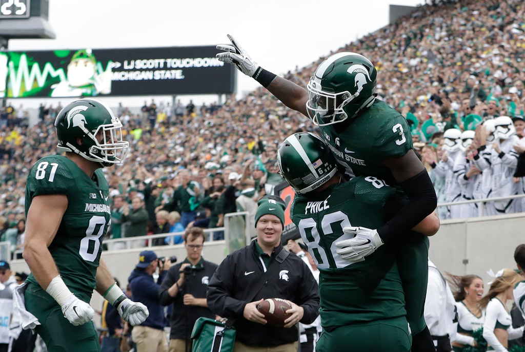 . Michigan State running back LJ Scott (3) celebrates his touchdown with teammate Michigan State tight end Josiah Price (82) during the first half of a college football game against Michigan, Saturday, Oct. 29, 2016, in East Lansing, Mich. (AP Photo/Carlos Osorio)