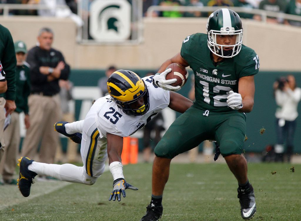 . Michigan State\'s R.J. Shelton, right, avoids a tackle attempt by Michigan\'s Nate Johnson (25) on a pass reception during the fourth quarter of an NCAA college football game, Saturday, Oct. 29, 2016, in East Lansing, Mich. Michigan won 32-23. (AP Photo/Al Goldis)