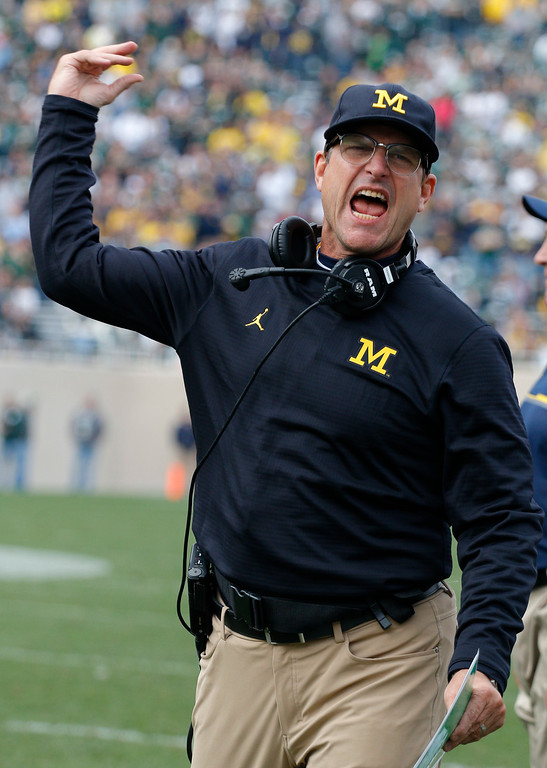 . Michigan coach Jim Harbaugh reacts during the fourth quarter of an NCAA college football game against Michigan State, Saturday, Oct. 29, 2016, in East Lansing, Mich. Michigan won 32-23. (AP Photo/Al Goldis)
