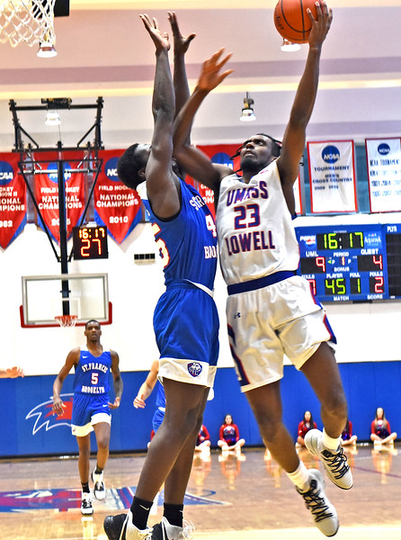 Going in for a lay-up is UML player #23-Christian Lutete as they play St Francis Brooklyn Terriers. SUN/ David H. Brow