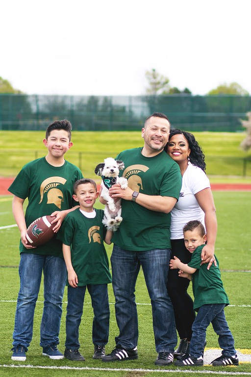 """. \""""This house bleeds green,\"""" said Mark Torres, who attended MSU along with his wife, Leyanna. The couple are shown here with their children Joaquin Torres, 13(left), Mark Anthony Torres jr, 8, Aden DiGiovanni, 5, and the family dog, Louis."""