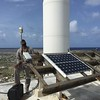 Anguilla airport maintenance supervisor Edwin Carty with the solar panels and metpack for CN51 on Sombrero Island. In the background, an unused lighthouse tower. (Photo/John Sandru, UNAVCO)