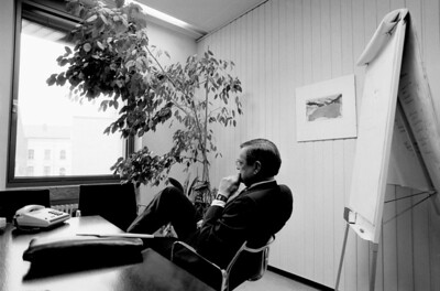 England.  London.  Senior executive in office of financial advisors Bain & Co, in contemplative mood.  Office plants, art, and flip chart.