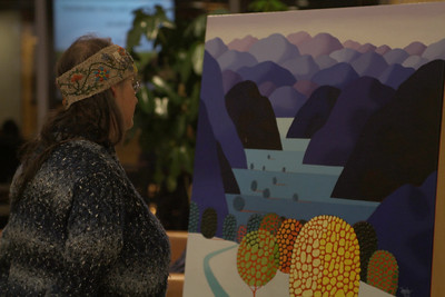 An attendee views one of the paintings on display.