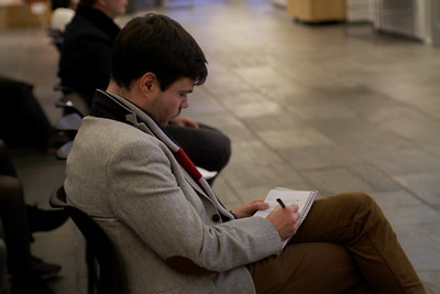Lecture attendee takes notes while listening to Holliday.