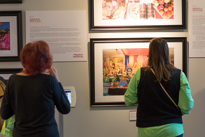 Guests view photos from the project Home in a New Place: Making Laos in Morganton, NC.