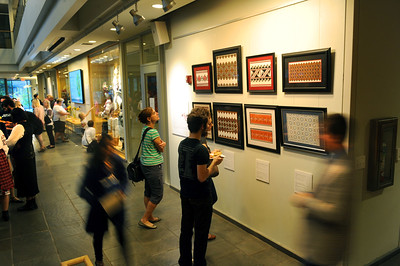 """Attendees view framed embroidery pieces demonstrating regional variations on display at the """"Image of Ukraine"""" exhibition.  Photo by Donn Young."""